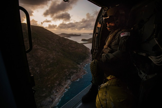 Leading Seaman Aircrewman Michael Sales surveys the coast from HMAS Parramatta's embarked MH-60R helicopter over the Whitsunday Islands.