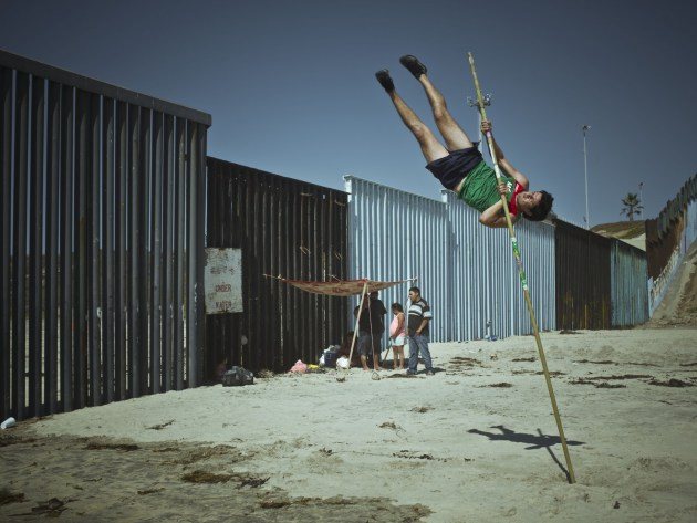 "© Cristina de Middel/Magnum Photos.  Jorge Luna, a professional Mexican pole vault jumper trains by the border fence on the beach of Tijuana. Tijuana, Mexico. 2018. ""I read on the internet that we shouldn't be scared of what we don't understand, but I probably shouldn't be relying on the internet to understand anything at all. Because of all the noise, these are confusing times on the surface, but also times where there is deep clarity in how to do good, and how to be potent and forceful in supporting the necessary changes to paradigms. The comfortable absurdity of the system is finally being questioned and it feels like there is room for dreaming of a future where the new logic that organizes the world is not that of the market, of historical power, of habit or of fear."""