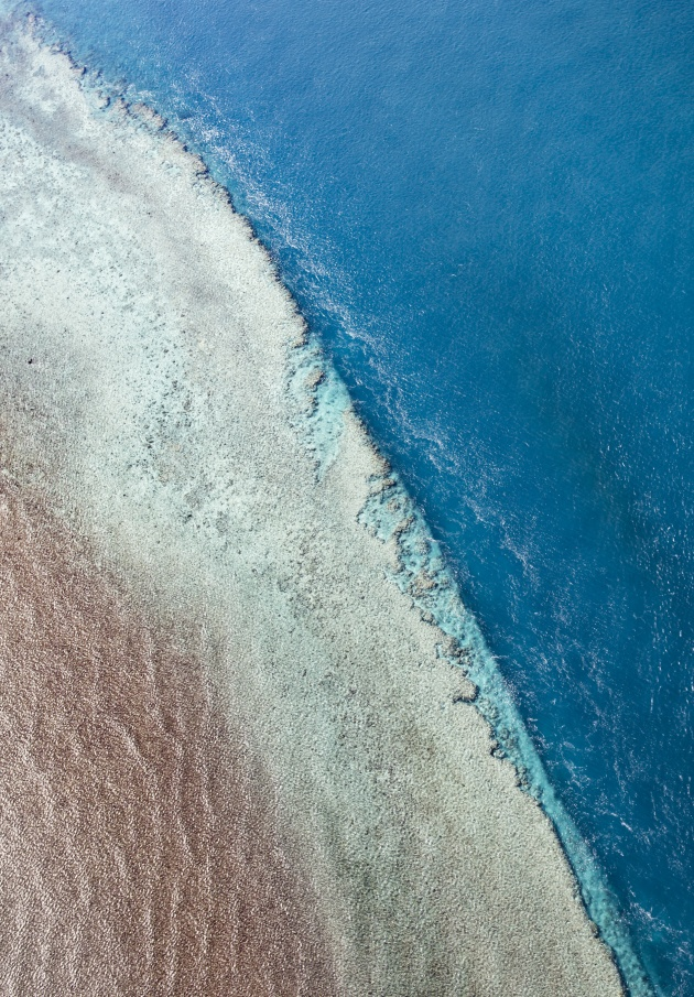 © Paul Hoelen. Layerings of reef and water merge together with equal amounts of texture. Great Barrier Reef, Whitsundays, Queensland.