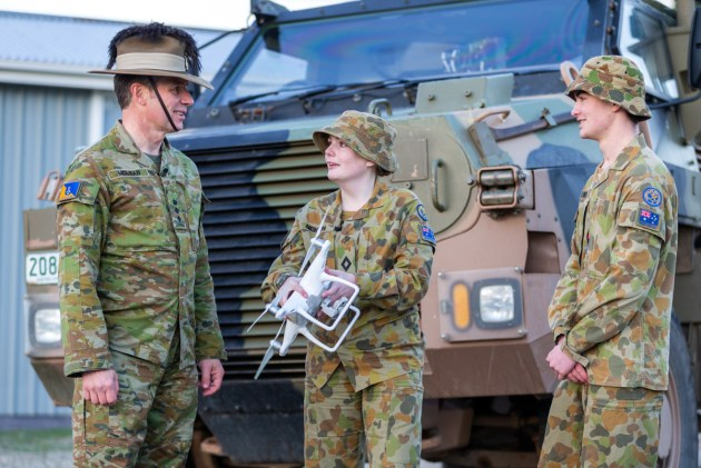 Colonel John Molnar (left) learns about drones from Australian Army cadets Cadet Under Officer Taylor Newton (centre) and National Cadet Under Officer Daniel Irwin.