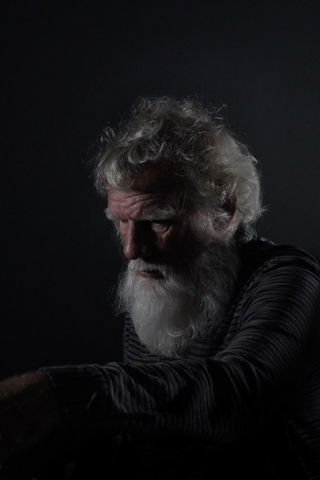 "Farmer, Fisher, Scholar and Scribe, 2019, by Andrew Baker. ""Bruce Pascoe, 72, fisherman, farmer, student and teacher. They are occupations with attributes that have no doubt contributed to his talent as a writer and proponent of Aboriginal history. He sits still and calm, but sees my every move."""