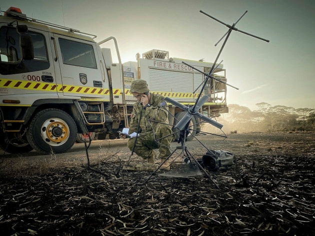 A soldier providing tactical satellite communications on fire grounds in Balladonia, WA. Defence