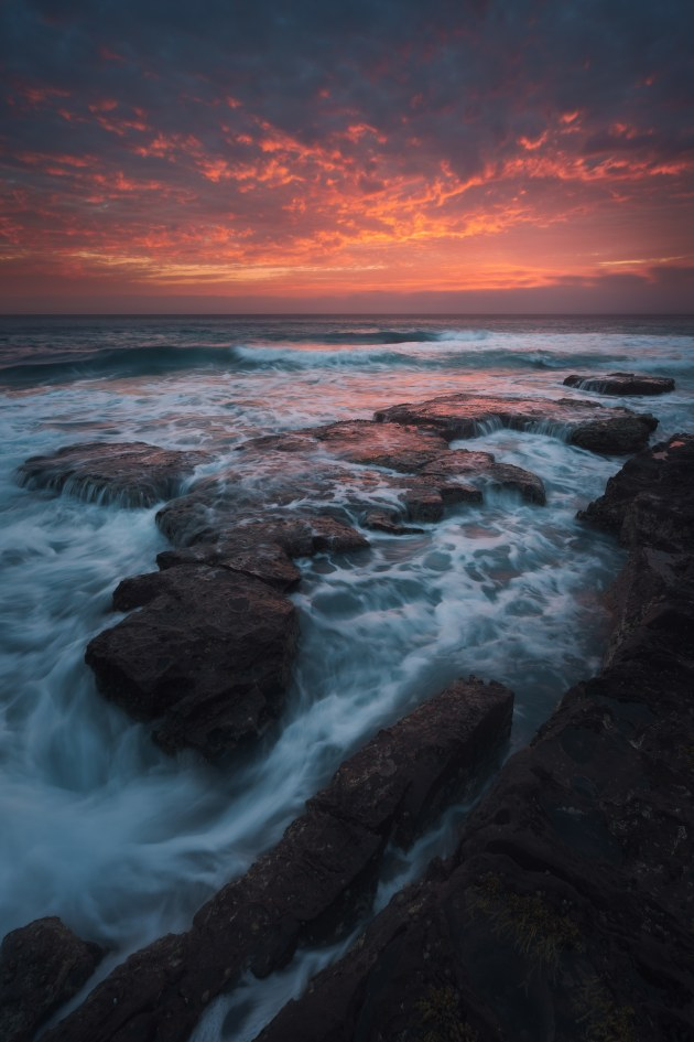 Shellharbour Sunrise: An explosion of colour over Shellharbour—the coastline of my childhood. While I would gravitate to the South Coast icons of Bombo Quarry and Cathedral Rocks (and still do), it's worth making time to explore the locations closer to home too. Sony A7R Mark II, 16-35mm f/4 lens @ 16mm. 1/6s @ f9, ISO 100.