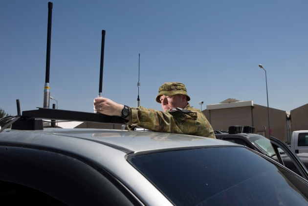 Major Geoffrey Small installs a silver shield electronic countermeasure device on a vehicle in Kabul, Afghanistan.