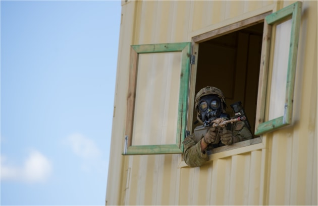A soldier from 2nd Battalion RAR leans through a window to check an area during the Duke of Gloucester Cup at Singleton Military Area in 2015.