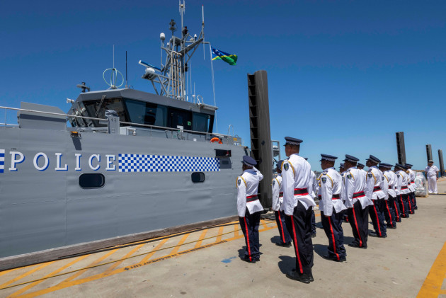 Members of the Gizo crew stand at attention whilst the Solomon Island national flag is raised.