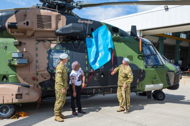 LTCOL Kim Gilfillan, WO1 Terry Hangan (right), and Wulgurukaba representative Brenton Creed unveil MRH 90 Gurindal, the Wulgurukaba word for 'vigilance'.