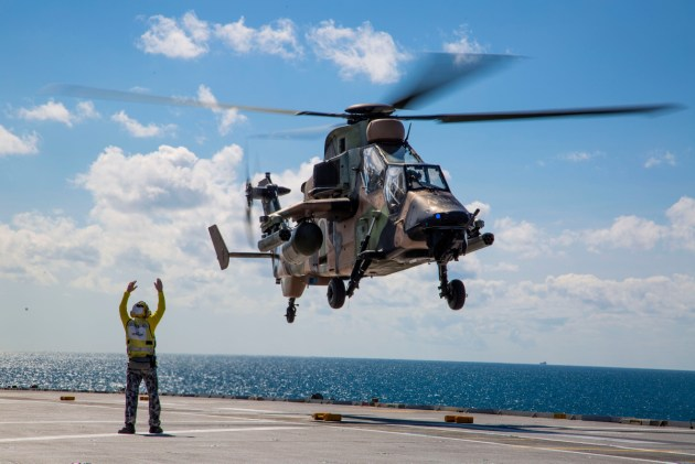 A Tiger ARH departs the flight deck of HMAS Canberra.