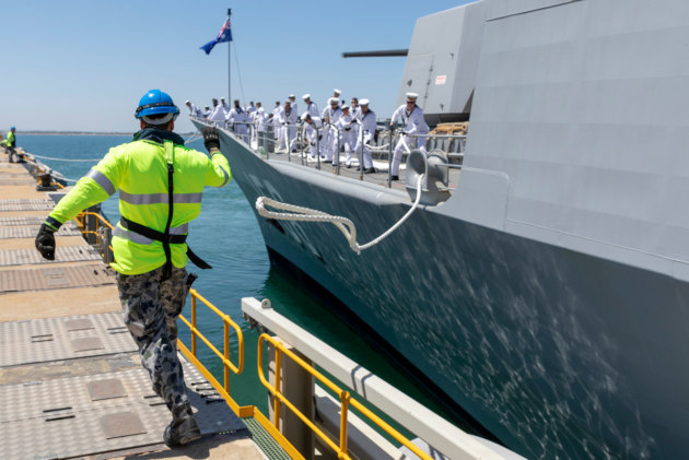 Able Seaman Boatswains Mate Josh Moore casts the berthing line as the ship departs.