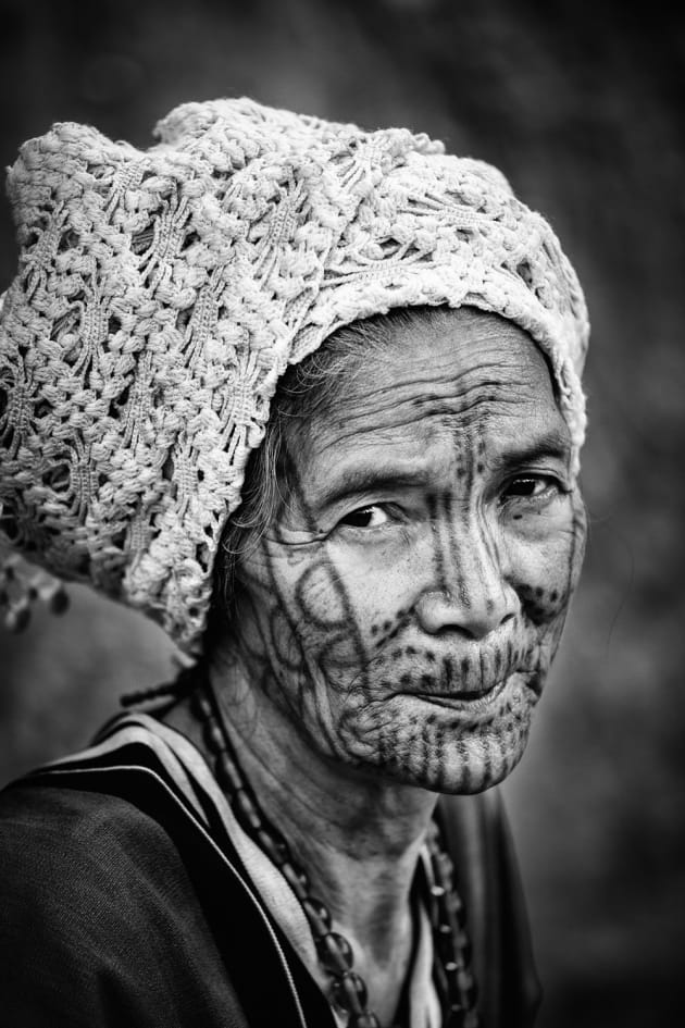 Tattoo faced woman from the remote hills of Chin State, Myanmar. I wanted to capture the tattoos, however the lighting was harsh and colour wasn't doing her face justice. Monochrome helped add definition to define her tattoo features. Canon 6D, Sigma 35mm f1.4 @ 35mm @ f/1.8, 200 ISO. Monochrome conversion, contrast and clarity with some dodging and burning of the tattoos adjusted in Adobe Lightroom.