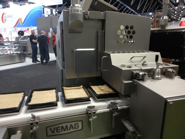 Vemag was showcasing new sausage processing and packing equipment designed to reduce human handling and speed processing. Its Alginate casing machine creates a continuous process for filling sausages using a vegetarian gel derived from algae which is solidified into a casing during processing. This reduces costs by eliminating the steps required to create natural and synthetic casings. The company has also recently launched an automated sausage packing line to completely replace manual handling.