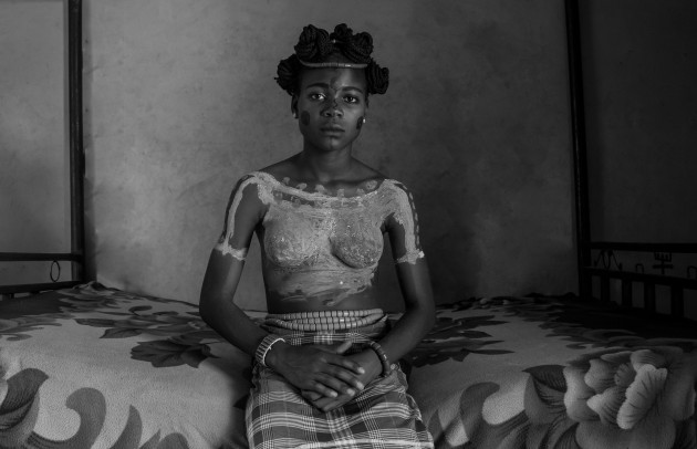 Category: Hidden Worlds. © Jenevieve Aken. Monankim, Cross River State, Nigeria, 2017. A teenage girl sits in her healing room, having recently been circumcised. This makes her, in the language of the Bakor people, a Monankim. After two weeks of recovery and feeding, she will be presented to the community as a sexually mature woman who has remained a virgin, ready for marriage. Some Bakor still celebrate this traditional rite of passage, but others oppose it, not least because of the health risks: the bleeding can be severe, and some Monankim do not survive it.